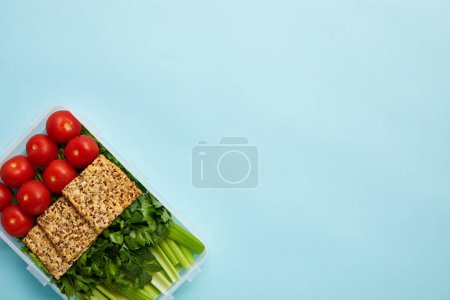 Photo for Top view of food container full of healthy meal with vegetables and cookies isolated on blue - Royalty Free Image