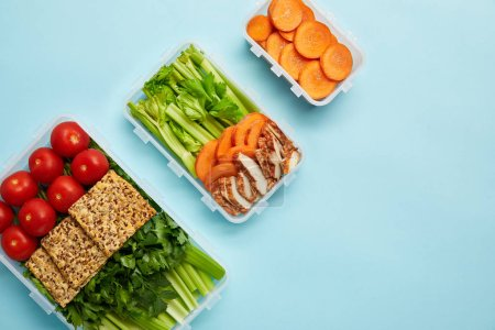 top view of arrangement of food containers with fresh healthy vegetables, meat and cookies isolated on blue