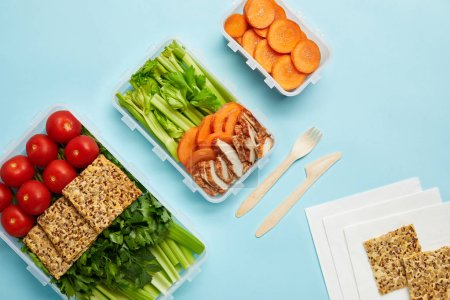 top view of arrangement of food containers with fresh healthy food and cutlery isolated on blue