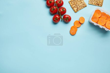 top view of arrangement of food container with fresh carrot slices, tomatoes and cookies isolated on blue