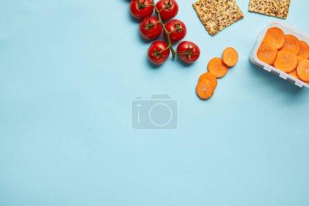 Foto de Vista superior del arreglo del envase de alimento con rodajas de zanahoria fresca, tomates y galletas aisladas en azul - Imagen libre de derechos