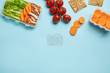 top view of arrangement of food containers with healthy food isolated on blue