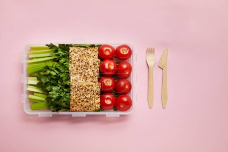 flat lay with healthy food arranged in food container and cutlery isolated on pink