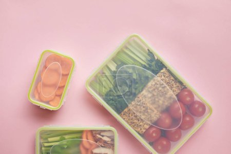 flat lay with healthy food arranged in food containers isolated on pink
