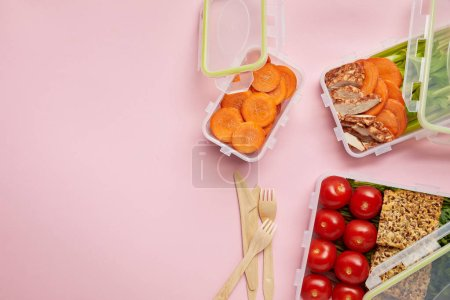 flat lay with healthy food arranged in food containers and cutlery isolated on pink