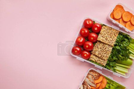 Photo for Flat lay with  fresh vegetables and cookies arranged in food containers isolated on pink - Royalty Free Image