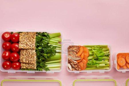 Foto de Lay Flat con verduras frescas y galletas dispuestas en recipientes aislados en rosa - Imagen libre de derechos