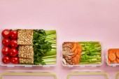 flat lay with  fresh vegetables and cookies arranged in food containers isolated on pink