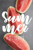 """flat lay with red watermelon pieces on grey concrete tabletop, with """"summer holidays"""" lettering"""
