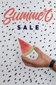 cropped shot of man holding watermelon piece in hands on white surface with summer sale lettering