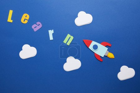 top view of learn lettering with clouds and rocket on blue background