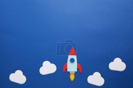 clouds and rocket on blue paper background with copy space