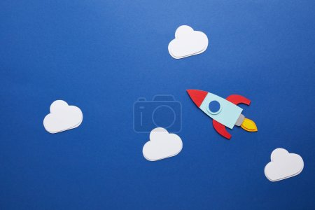 white clouds and rocket on blue background