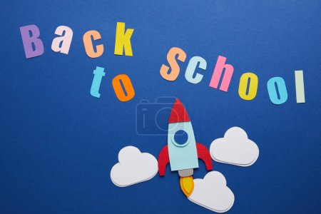 top view of back to school lettering with clouds and rocket on blue background