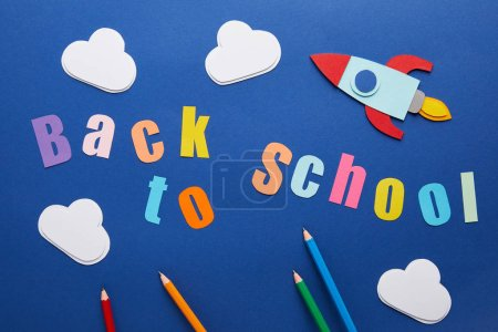 top view of back to school lettering with pencils, clouds and rocket on blue background