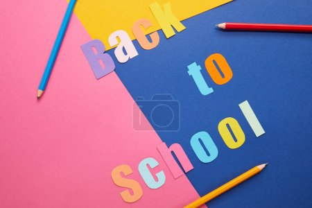 colorful back to school lettering with pencils on paper background