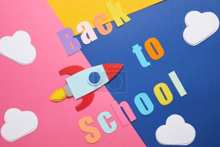 back to school lettering with clouds and rocket on colorful paper background