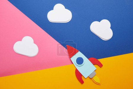 top view of clouds and colorful rocket on creative paper background