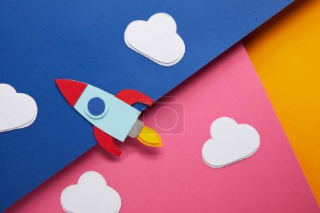 top view of clouds and rocket on colorful paper background