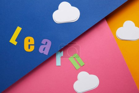 """learn"" lettering with clouds on colorful paper background"
