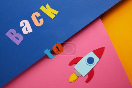 "flat lay with ""back to"" lettering and rocket on colorful paper background"