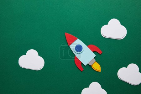 top view of rocket and clouds on green chalkboard