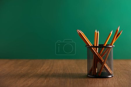 Photo for Pencils on wooden table with green chalkboard on background - Royalty Free Image
