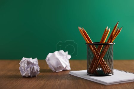 pencils, copybook and crumpled papers with green chalkboard on background