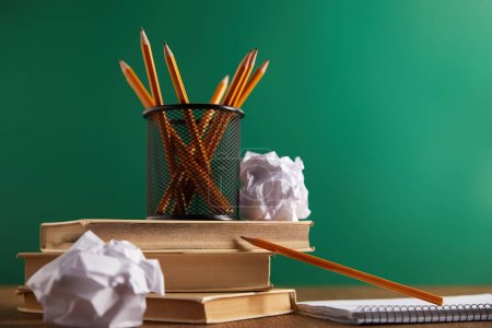 books, crumpled papers and pencils with green chalkboard on background