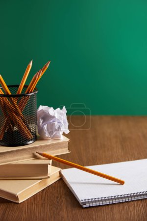 books, copybook, crumpled paper and pencils on wooden table