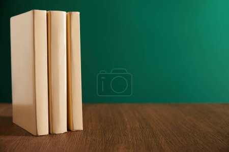 three books on wooden table with chalkboard on background