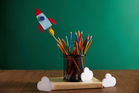 colorful pencils, rocket, clouds on book with chalkboard on background
