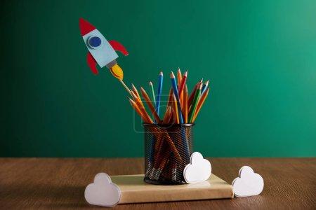 Photo pour Crayons colorés, fusée, nuages sur livre avec tableau sur fond - image libre de droit
