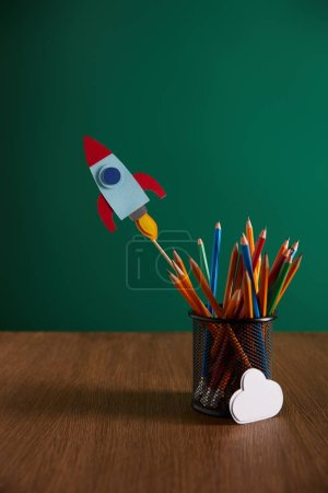colorful pencils, rocket, cloud sign on wooden table with chalkboard on background
