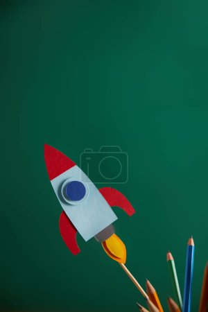 pencils and colorful rocket with green chalkboard on background