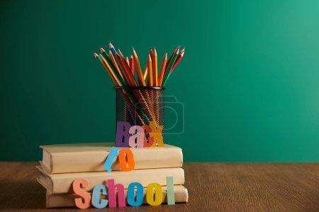 Photo pour Crayons colorés sur les livres avec retour à l'école de lettrage, tableau noir sur fond - image libre de droit