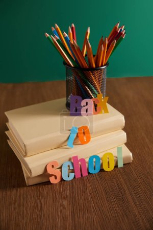 pencils and books on wooden table with back to school lettering