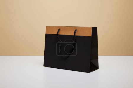 one black shopping bag on white table
