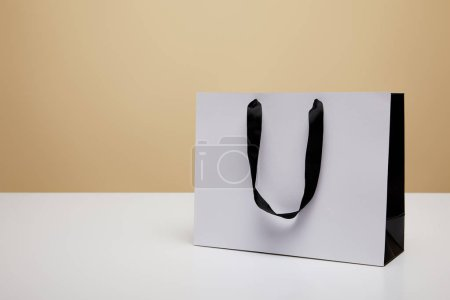 one white shopping bag on white table isolated on beige
