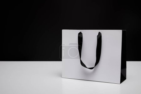 one white paper shopping bag on white table isolated on black