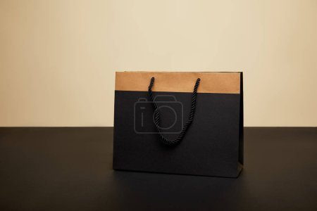 one black shopping bag on black table isolated on beige