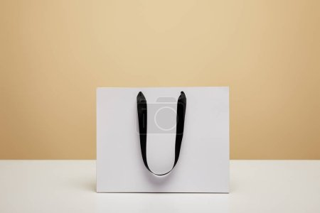 one white shopping bag on white tabletop isolated on beige