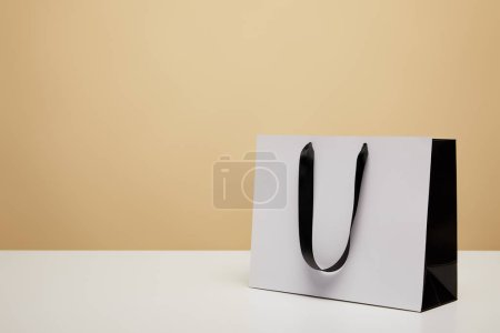 Photo for One white shopping bag with black handle on white table isolated on beige - Royalty Free Image