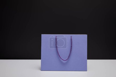 Photo for One violet shopping bag on white table isolated on black - Royalty Free Image