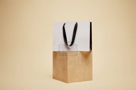 Photo for One shopping bag on wooden cube isolated on beige - Royalty Free Image