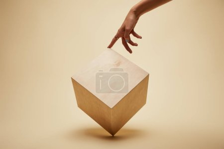 Photo for Cropped image of woman touching wooden cube on beige - Royalty Free Image