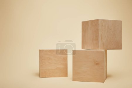 Photo for Three brown wooden cubes isolated on beige - Royalty Free Image