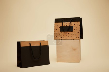 Photo for One shopping bag on wooden cube, black paper bag on beige surface - Royalty Free Image