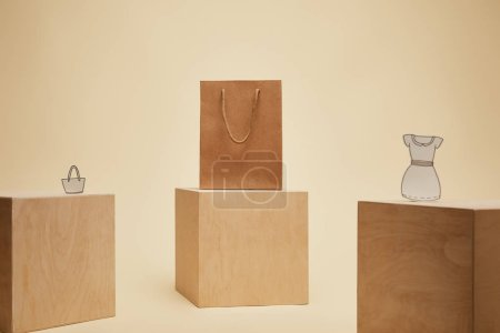 paper shopping bag, paper bag and paper dress on wooden cubes isolated on beige