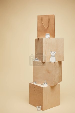 shopping bag and paper clothes on wooden cubes isolated on beige